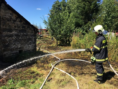 Hasiči zasahovali u požáru tújí blízko domu na Všeni
