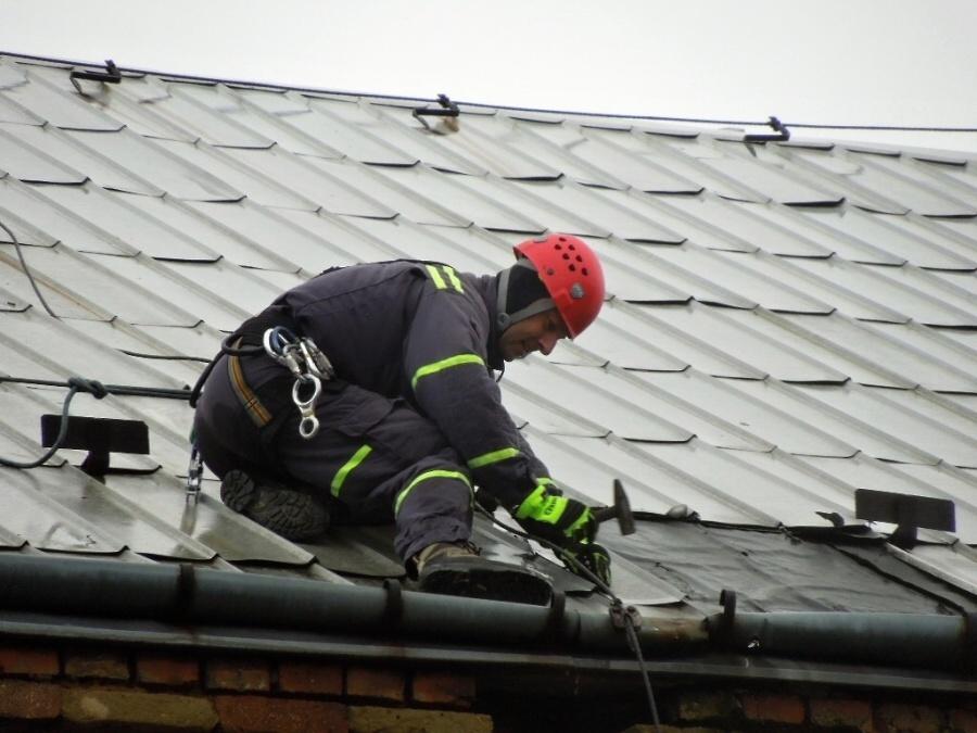 Skupina českolipských profesionálních hasičů přibíjí plechy na domě v Kamenickém Šenově<br>Autor: HZS Libereckého kraje, PS Česká Lípa