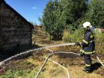 Hasiči zasahují u požáru tújí a suché trávy v obci Všeň